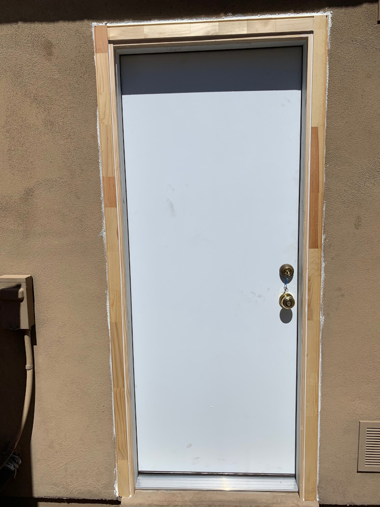 Licensed worker installing a replacement door and frame